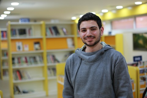 Smiling young man stands in library