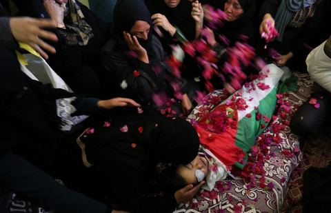 Women lean over and throw flower petals on body of boy shrouded in Palestinian flag
