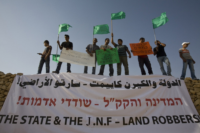 """Men carrying signs and flags stand above banner reading """"State & the JNF - Land Robbers"""" in Arabic, Hebrew and English"""