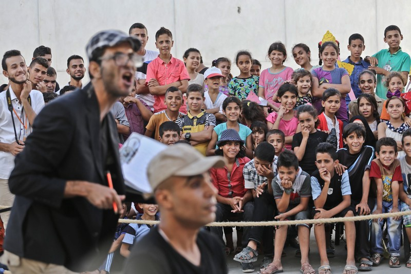 Crowd of boys and girls watch actors perform in street