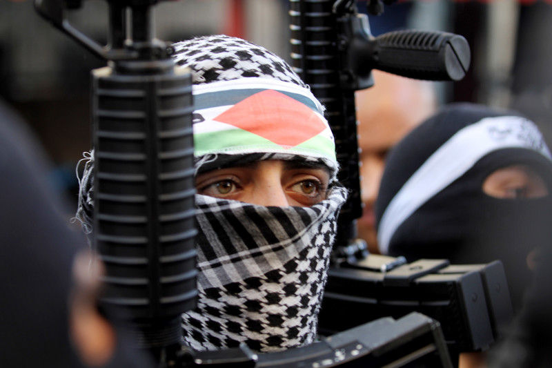 Young man wearing checkered scarf around his head and face holds rifle