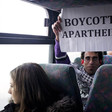 Basil al-Araj sits on bus behind Israeli woman while holding up a sign reading Boycott Apartheid