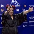 Woman dressed in black waves a blue and white flag in front of a backdrop featuring corporate logos.