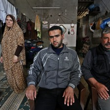 Father and son sit in chairs as mother stands behind them next to clothing line