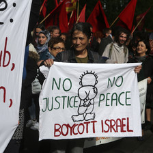 A woman holds a banner reading No Justice No Peace Boycott Israel amid crowd