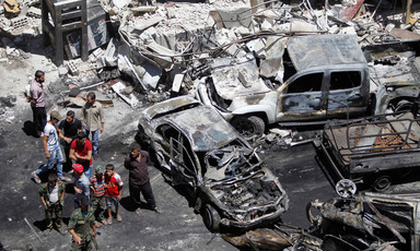 Aerial view of people standing near burnt-out cars and shelled buildings