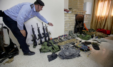 Man in uniform gestures towards display of rifles and other weapons