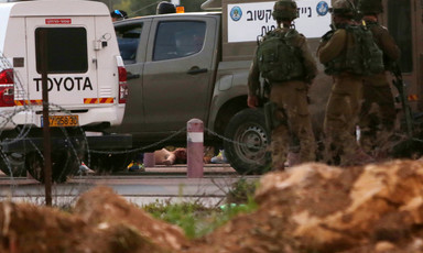 Mahmoud Shaalan's body lays on road behind Israeli military vehicles and group of soldiers