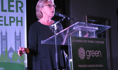 Green Party leader Elizabeth May speaks into microphone at podium