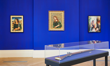 Installation view of three works on canvas on wall with vitrine containing rifle in foreground