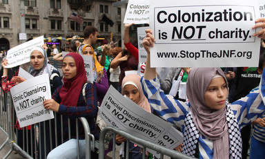 Young women hold up signs reading: Colonization is NOT charity www.stoptheJNF.org