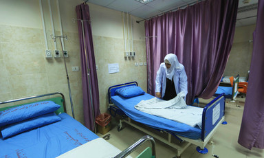 A woman nurse folds a sheet on a bed in an empty hospital room